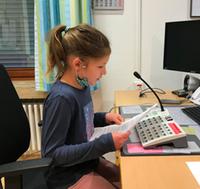 Ein Mädchen spricht die Neuigkeiten in ein Mikrofon