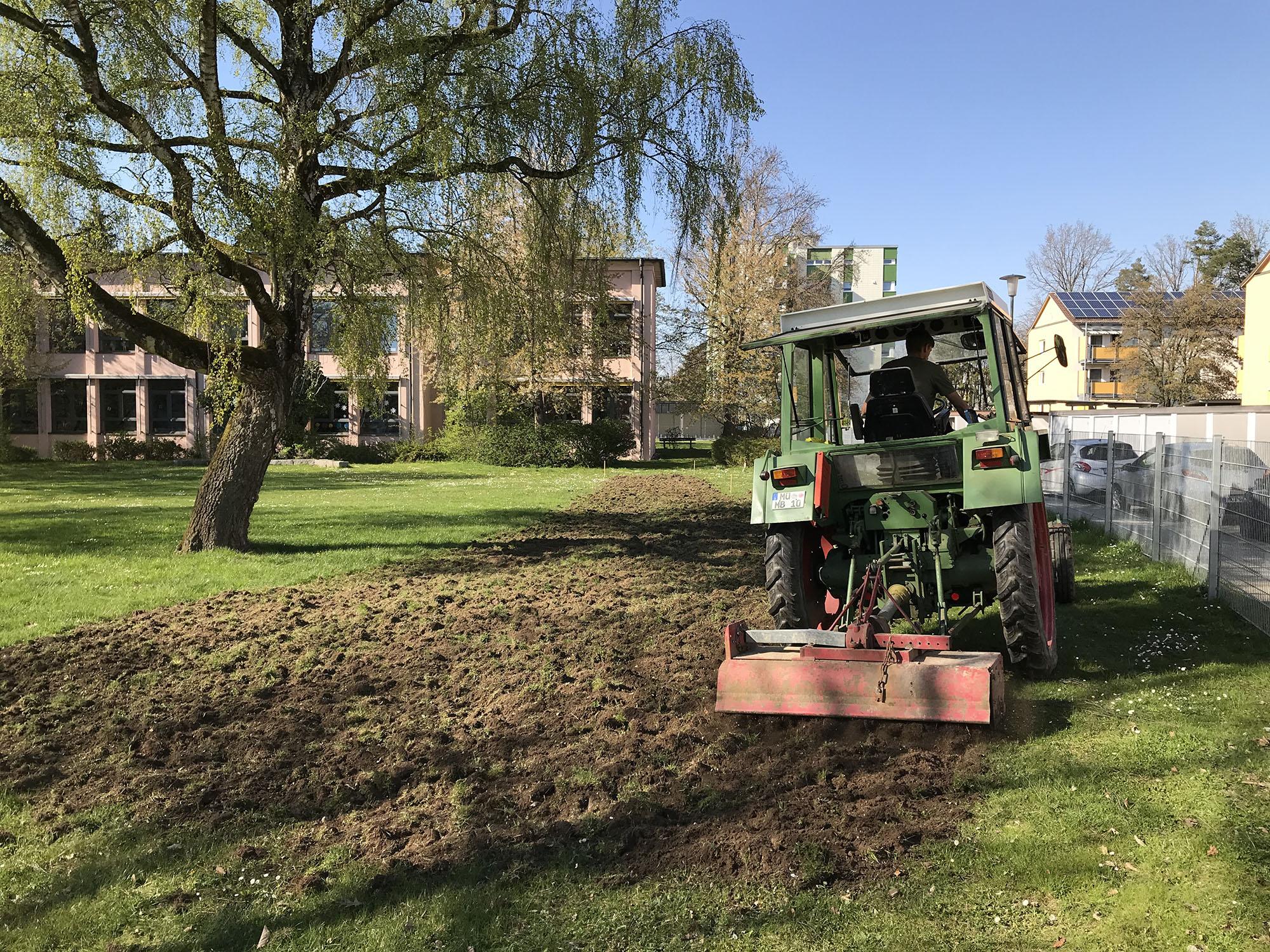 Ein Traktor bereitet den Boden für die Blumenwiese vor